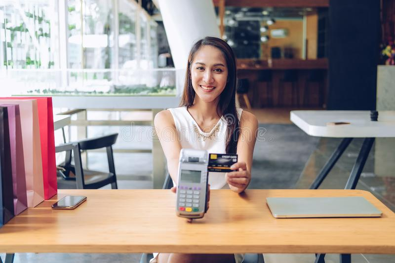 Woman with credit card swiping machine & shopping bags on table. payment with nfc technology. Woman with credit card swiping machine & shopping bags on table stock photos
