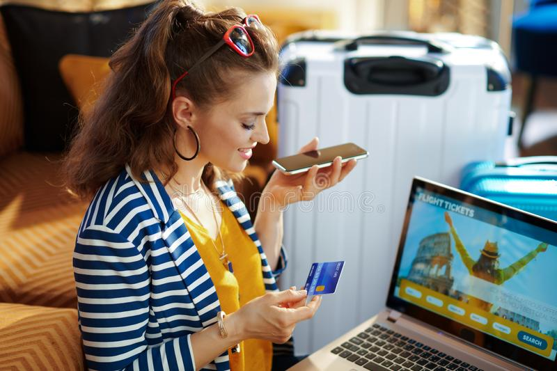 Woman with credit card talking on phone to buy airplane tickets. Side view of happy stylish woman in striped jacket with credit card talking on a smartphone to royalty free stock photos