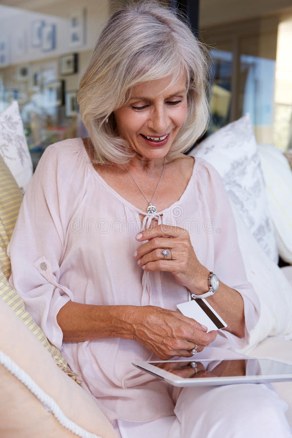 Woman with credit card and touch screen tablet. Portrait of older woman with credit card and touch screen tablet royalty free stock photos