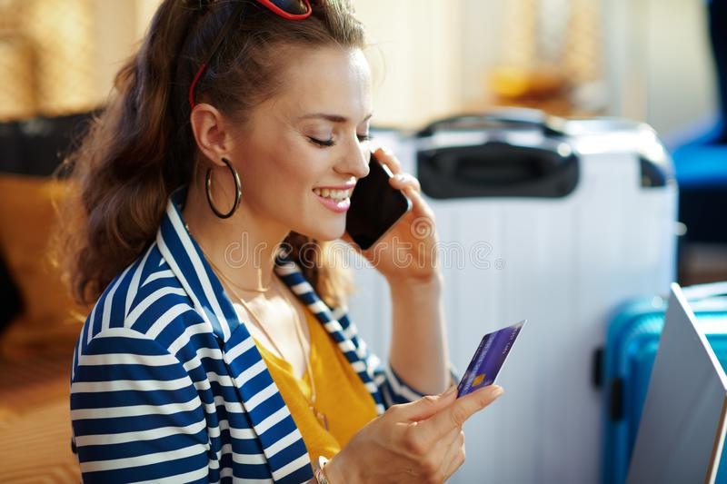 Woman with credit card using cell phone to buy airplane tickets royalty free stock photos