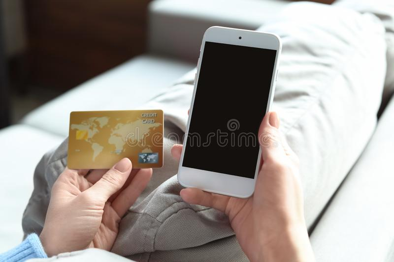 Woman with credit card using mobile phone at home royalty free stock photography