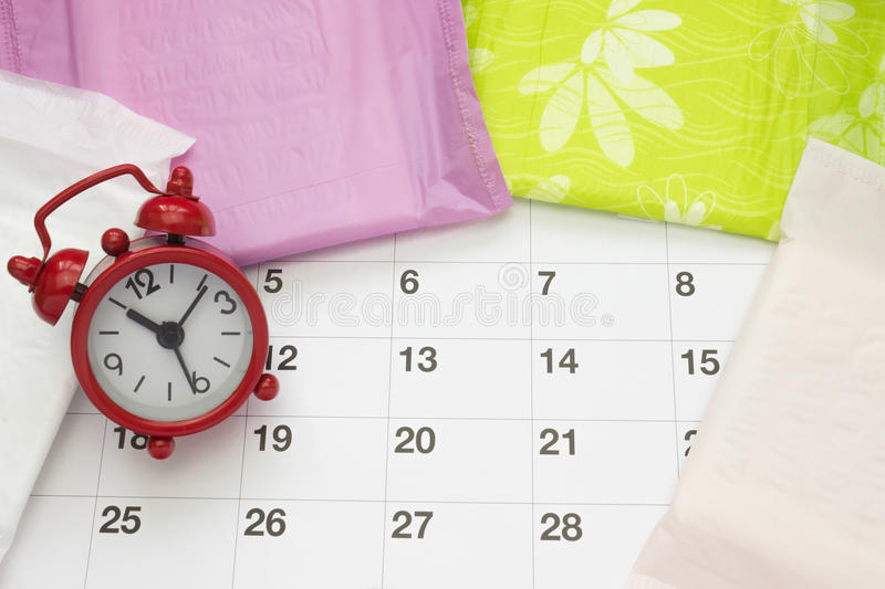 Woman critical days, gynecological menstruation cycle, blood period. Menstrual sanitary soft pads, calendar and a clock. Woman hyg. Iene protection for menstrual stock photo