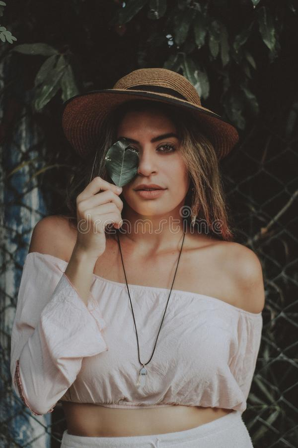 Woman in Crop Top Holding Leaf Covering Right Eye stock photo