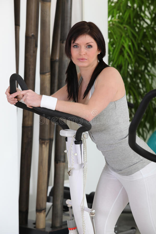 Woman on cross trainer royalty free stock images
