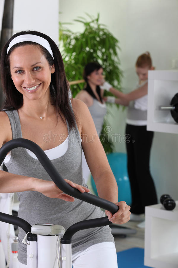 Woman on cross trainer royalty free stock image