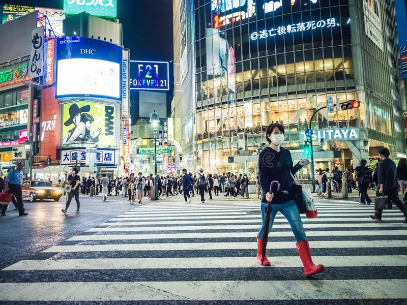 Woman Crossing after Crowds at Shibuya Crossing Japan stock photos