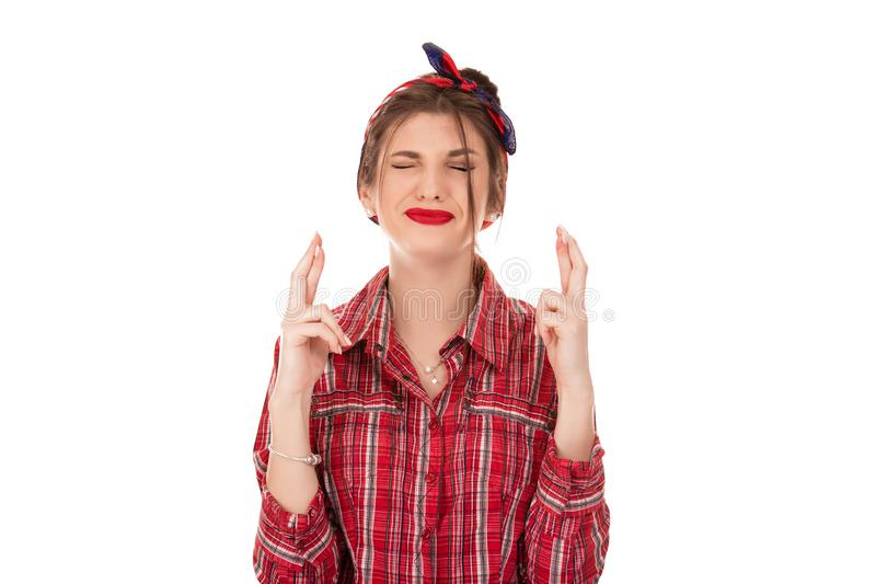 Woman crossing fingers wishing something badly, hoping for the best stock image