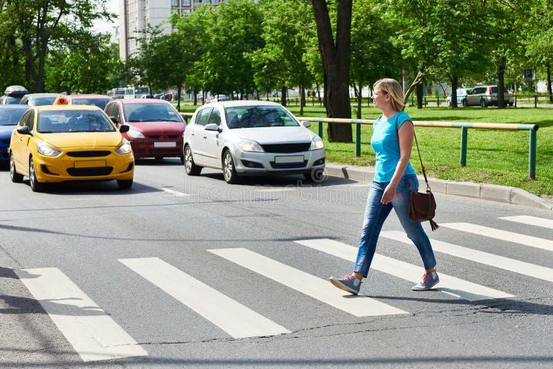 Woman crossing street at pedestrian crossing stock photo