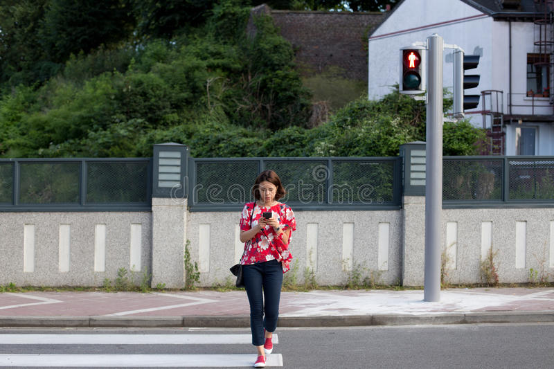 Woman crossing the street on red light royalty free stock images