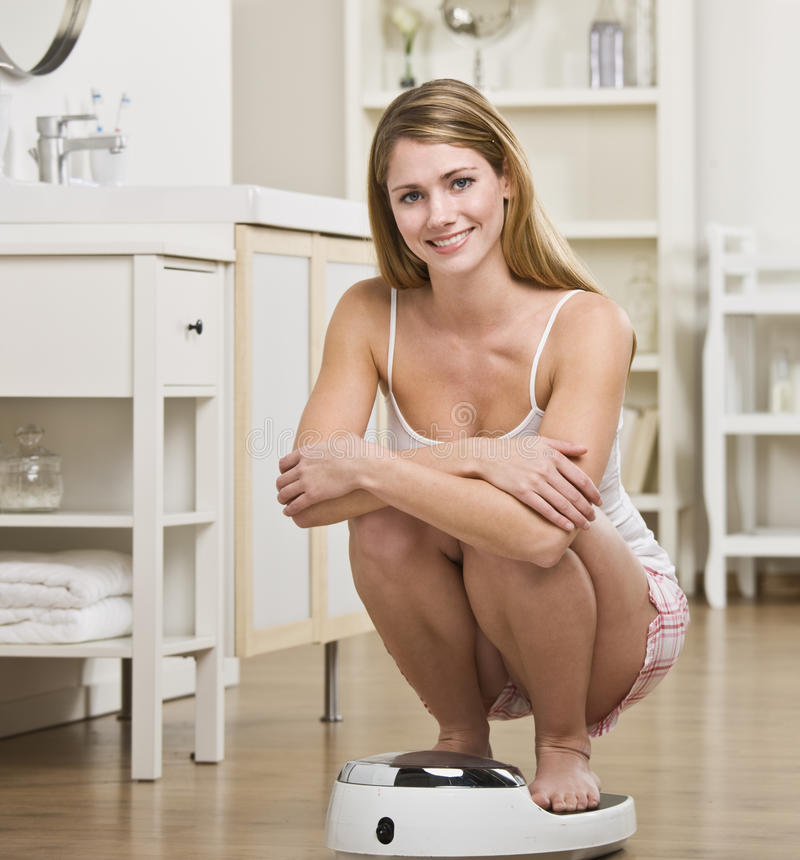 Woman Crouching on Scale royalty free stock image