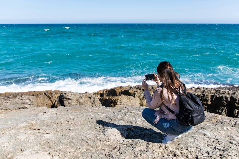 Woman crouching taking pictures of shore with smart phone stock image