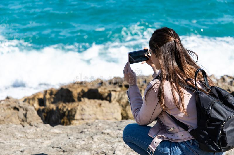 Woman crouching taking pictures of shore with smart phone royalty free stock images