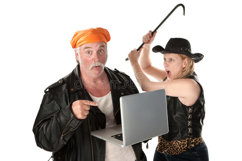 Woman with crowbar threatening man. Looking at something risque on laptop computer royalty free stock images
