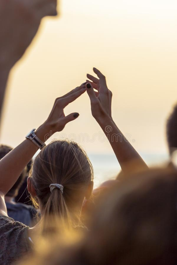 Woman in the crowd claps with hands up. A blonde woman is in the crowd during a public event and is clapping her hands up in the air. Sky is painted with orange stock image