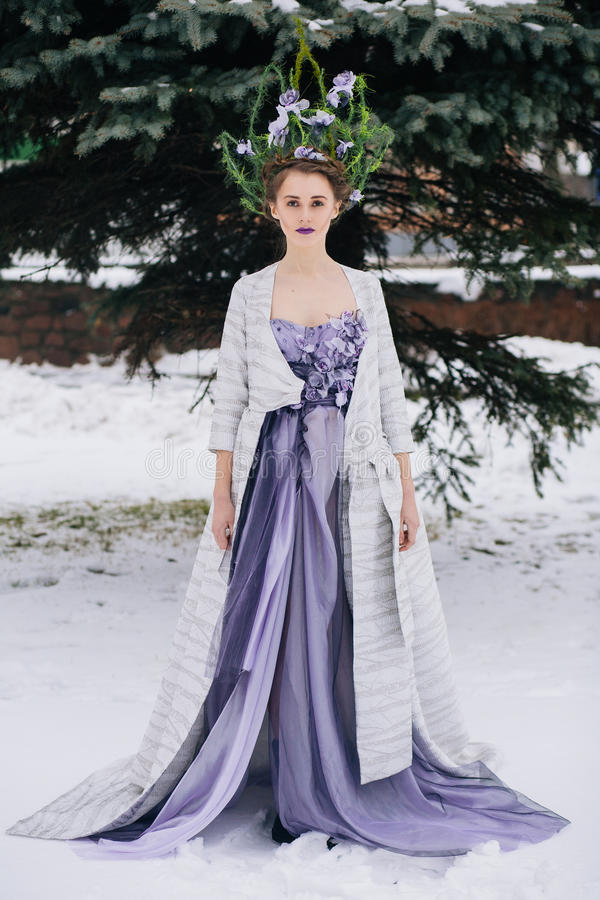 Woman with crown in forest. Outdoor full body shot of beautiful young woman in fashion elegant designer purple dress with crown in winter royalty free stock images