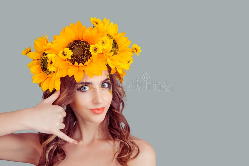 Woman in crown from sunflowers making call me gesture royalty free stock image