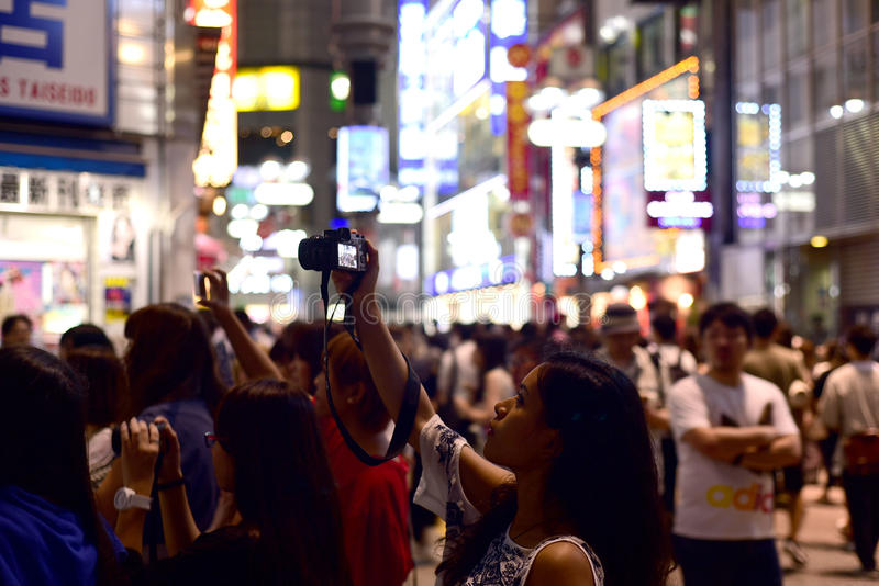 A WOMAN IN A CROWD TAKING PHOTOS IN A BUSY CITY. A woman in a crowd holds a camera and taking photos at night in a busy city. Photo taken in Shibuya, Tokyo royalty free stock photography