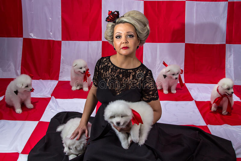 Woman in crown with white puppies royalty free stock photos