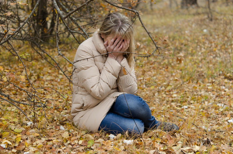 A woman crying in the autumn forest with yellow leaves royalty free stock photography