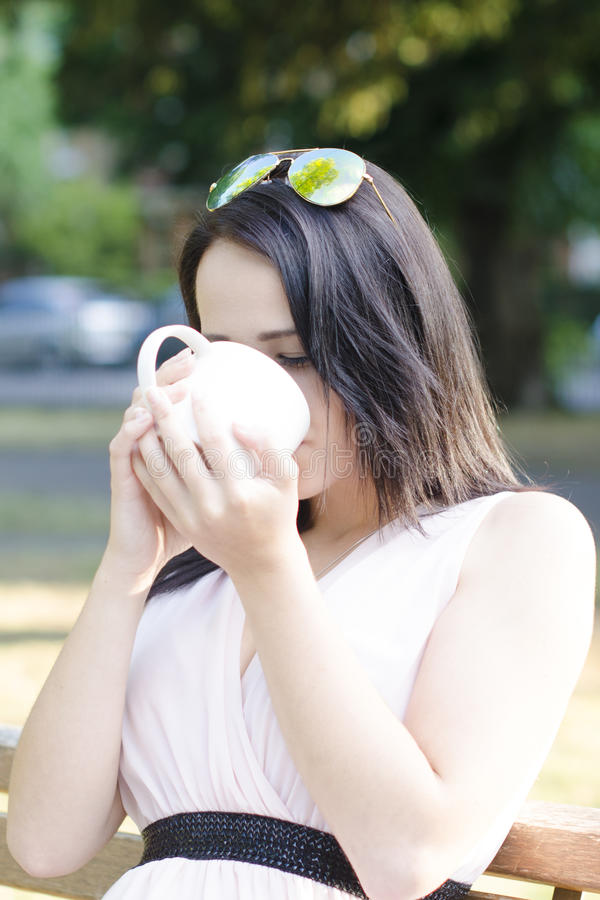 Woman with cup of coffee in a park and drink it stock photos