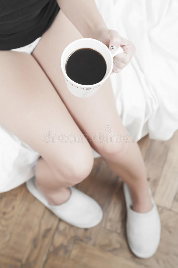 Woman With A Cup Of Coffee And Slippers Stock Image