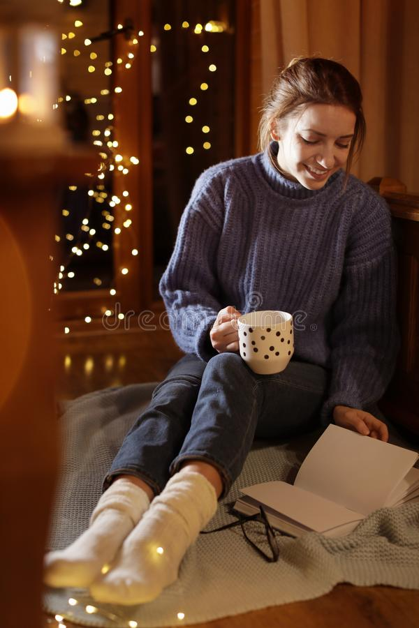 Woman with cup of hot beverage reading book at home. In winter evening royalty free stock image