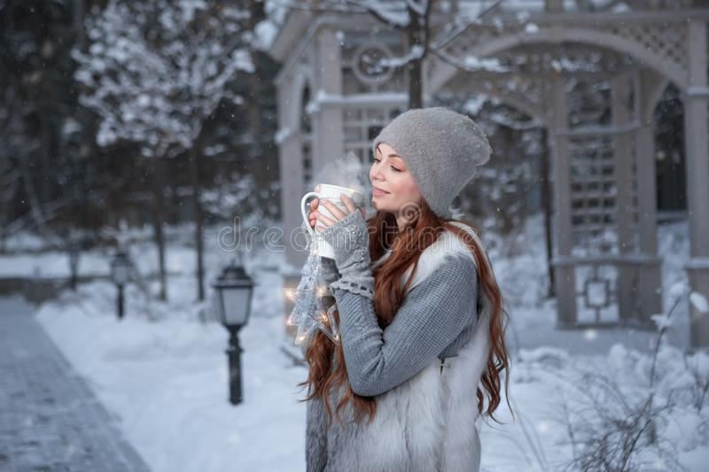 Woman with cup of tea in a park. Christmas girl outdoor portrait. Winter woman with cup of tea in a park stock photos