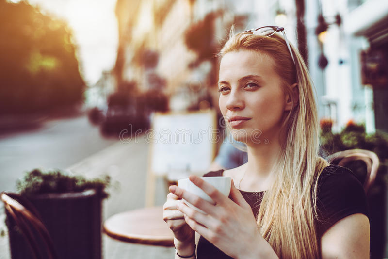 Woman with cup of tea in street cafe stock photos