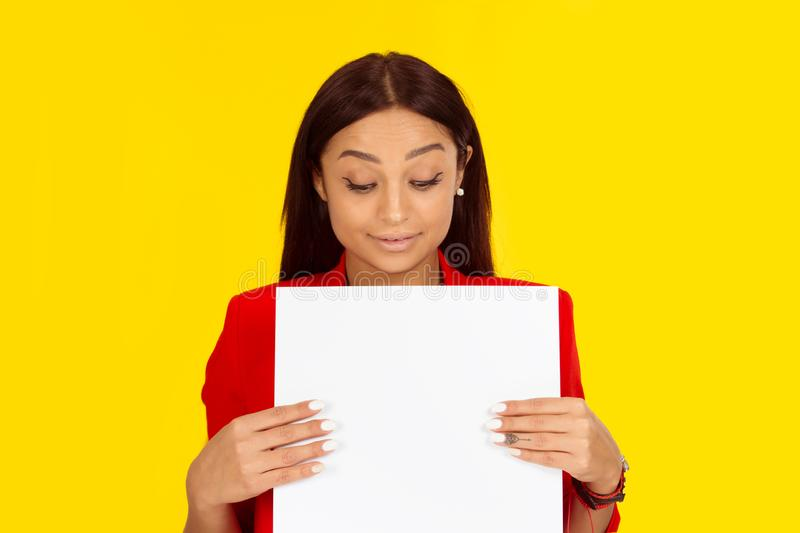 Woman curious looking down at a white blank paper board royalty free stock image