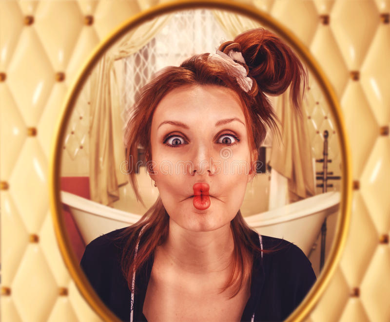 Woman with curled lips. Strange woman with curled lips looks in the mirror royalty free stock photography