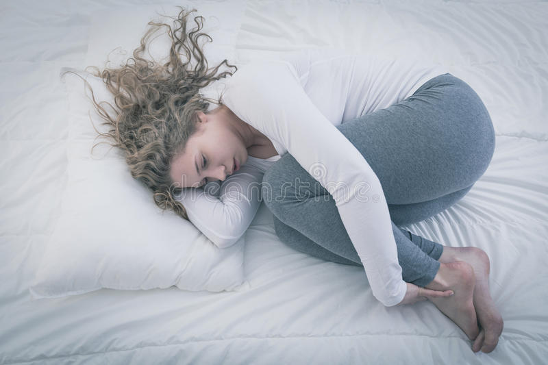 Woman curled up in bed royalty free stock image