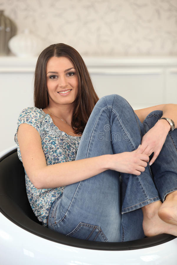 Woman curled up in a chair. Young woman curled up in a chair royalty free stock photo