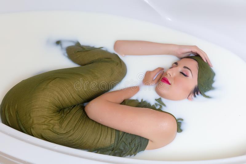 Woman curled up in milk bath. Relaxed young woman lying in a milk bath wet dressed royalty free stock photos