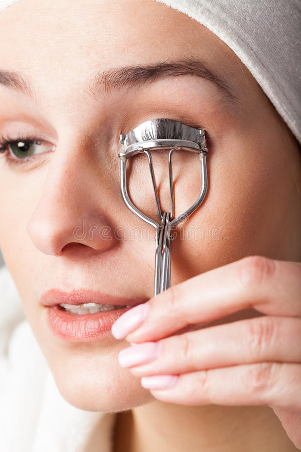 Woman with curler. Woman using curler to have beautiful eyelashes stock image