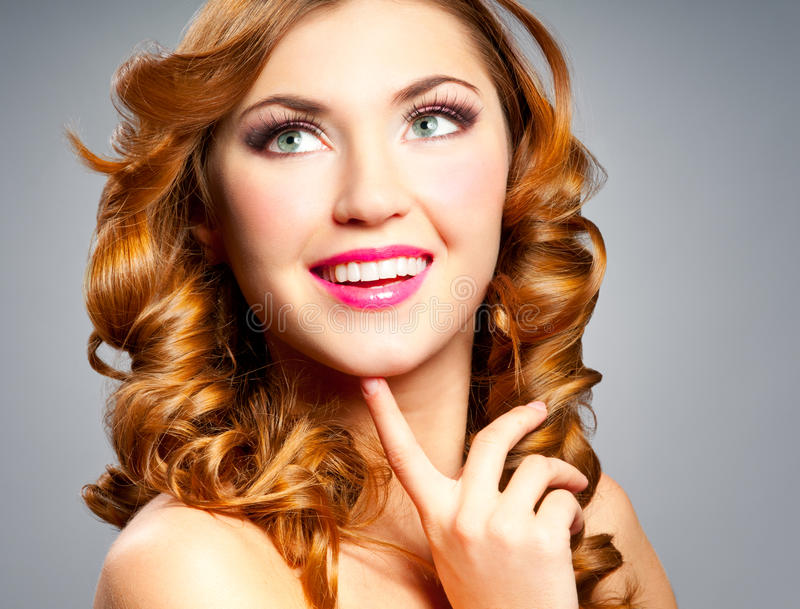 Woman with curly hair. Beautiful happy woman with gold curly hair stock image