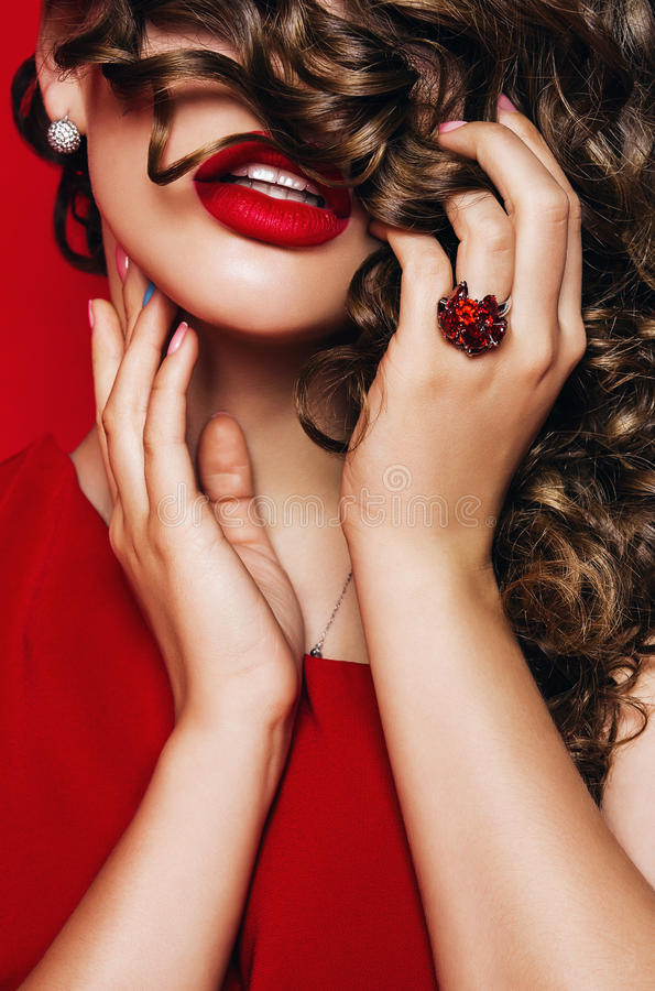 Woman with curly hair on eyes and ruby ring royalty free stock image