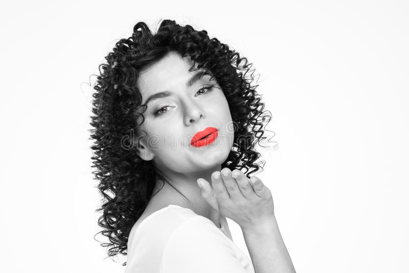 Woman with curly hair sending air kiss royalty free stock images