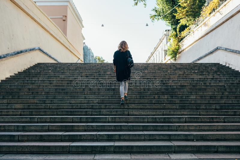 Woman with curly hair up the stairs royalty free stock photo