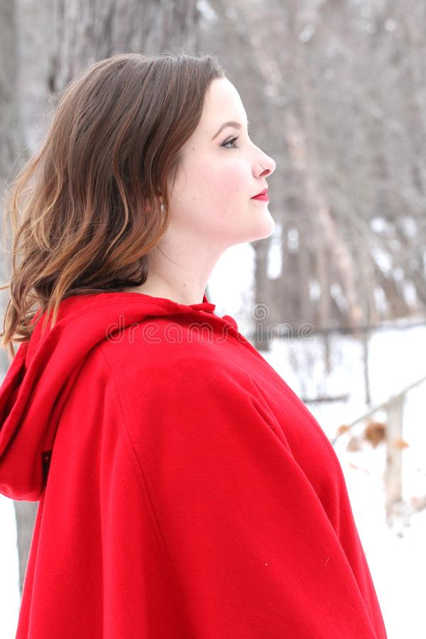 Woman with curly, long hair in vintage red cape looks forward in outdoor winter scene royalty free stock photos