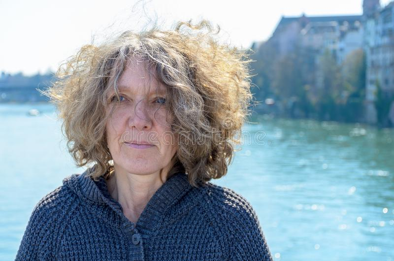 Woman with curly tousled hair outdoors. On a bridge standing with her back to the water looking thoughtfully stock photo