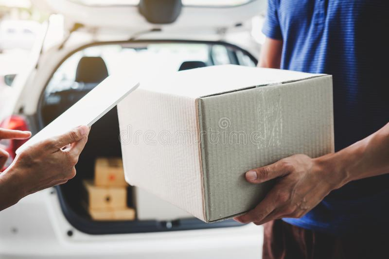 Woman customer appending signature in digital tablet and receiving a cardboard boxes parcel from delivery service courier, Home royalty free stock image