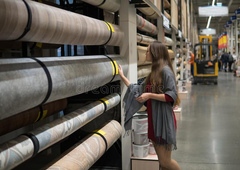 Woman customer choosing linoleum flooring in hypermarket stock photos