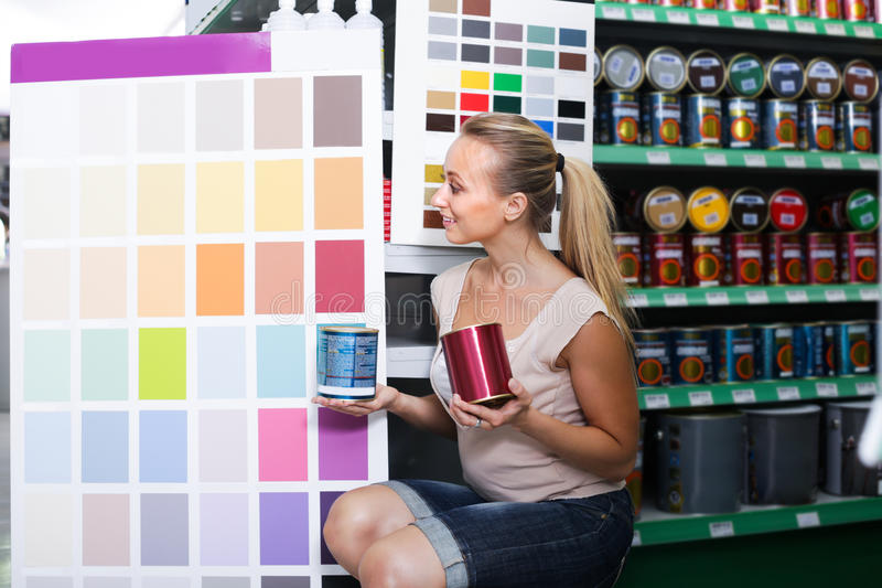 Woman customer in housewares hypermarket. Smiling young woman looking at color palette in housewares hypermarket royalty free stock images