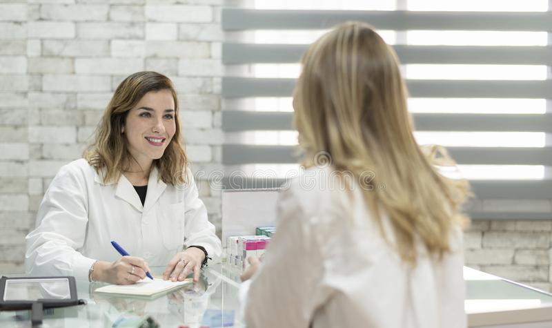 Woman customer in pharmacy with doctor woman ready for prescript stock photography