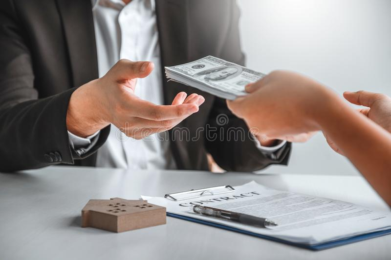 Woman customer sign agreement buying home ,salesman receive money after good deal after successful loan contract.  royalty free stock photos