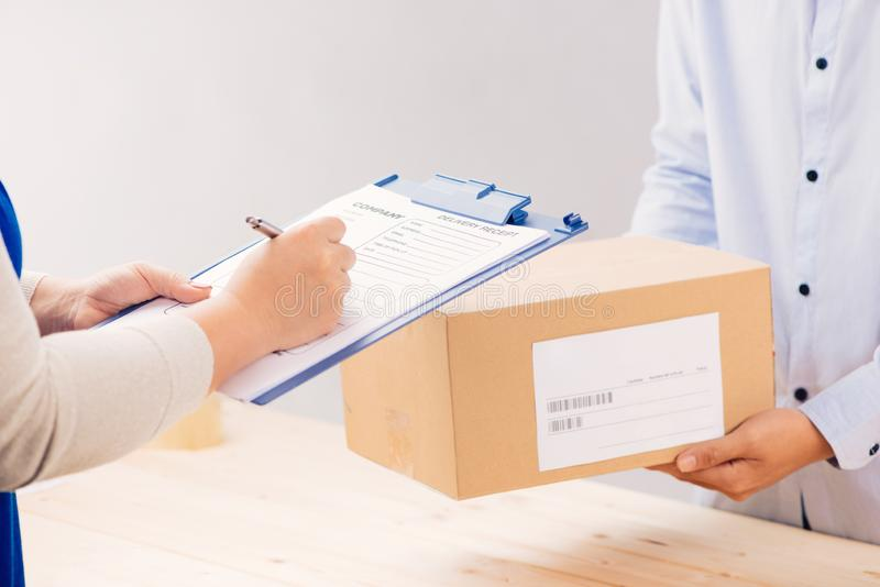 Woman customer signing receipt and receiving the parcel from delivery man. Business and logistic concept stock photography
