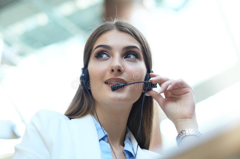 Woman customer support operator with headset and smiling. royalty free stock image