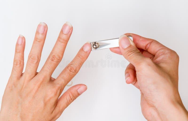 Woman cut fingernail. Woman cut fingernail with herself stock photos