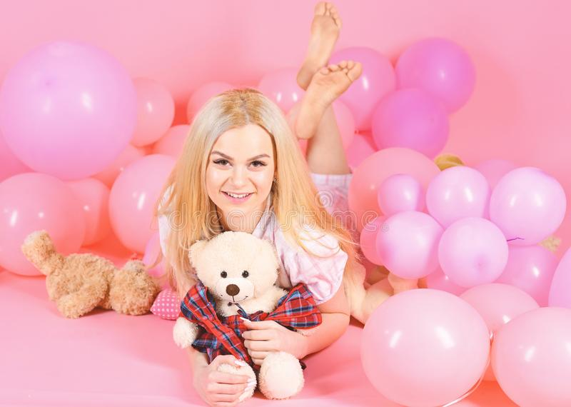 Woman cute celebrate birthday with balloons. Girl in pajama, domestic clothes lay near air balloons, pink background. Birthday girl concept. Blonde on smiling royalty free stock images