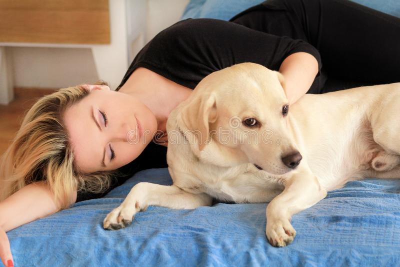 Woman with cute dogs at home. Handsome girl resting and sleeping with her dog in bed in bedroom. Owner and dog sleeping in sofa. royalty free stock photography